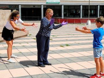 """Un niño y su madre dan un """"abrazo en la distancia"""" a la abuela en una plaza de Las Palmas de Gran Canaria durante el estado de alarma"""