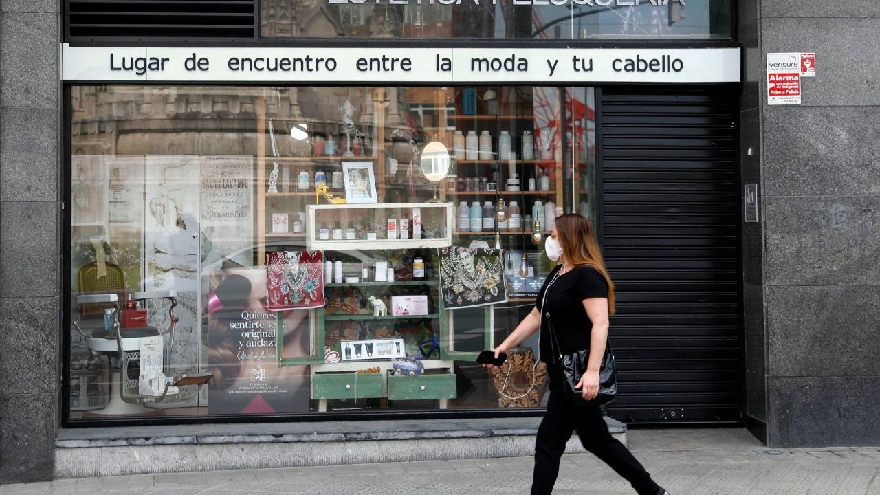 Una mujer pasea ante una peluquería durante la crisis del coronavirus
