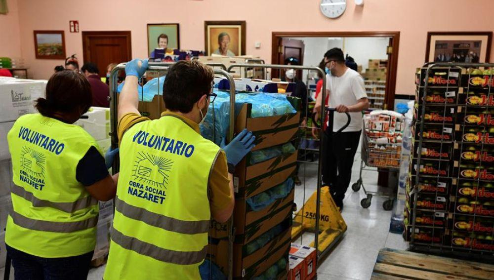 Varios voluntarios preparan lotes de alimentos para personas necesitadas