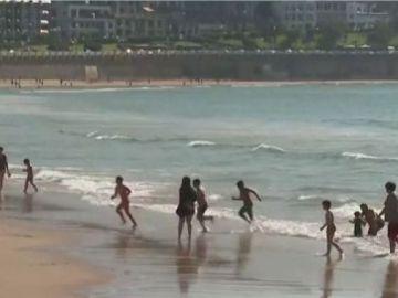 Niños abandonan a la carrera el agua en la playa de Donostia