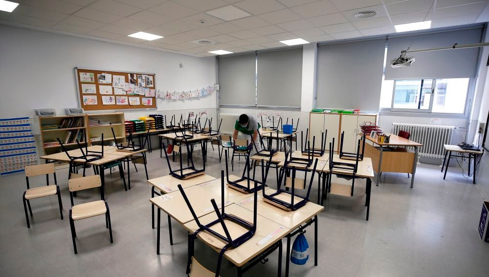 Una trabajadora del servicio de limpieza desinfecta las sillas y los pupitres de una clase de infantil de un colegio en Valencia
