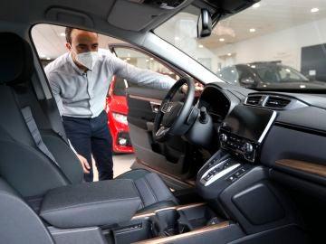 Un hombre con mascarilla ve un coche en un concesionario