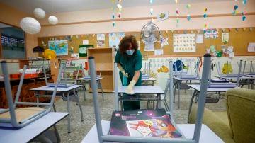Una limpiadora desinfecta el mobiliario de un colegio