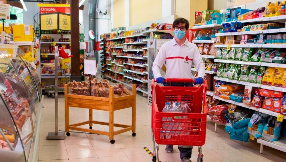 Un voluntario de la Cruz Roja hace la compra en un supermercado de Palma de Mallorca