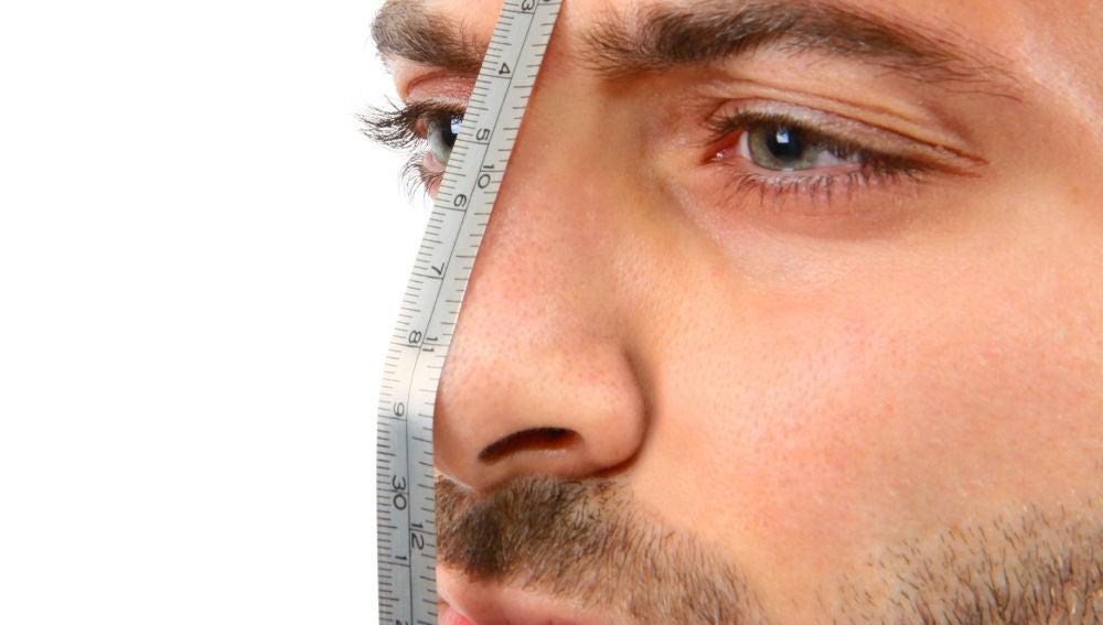 Un hombre se mide la nariz