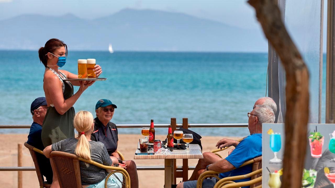 Una camarera sirve unas bebidas en una terraza de L'Escala (Girona)