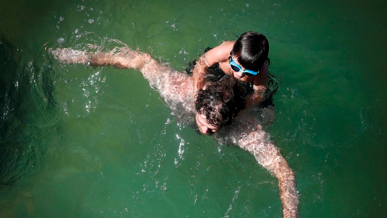 Un hombre y su hijo se bañan en la playa de La Concha de San Sebastián
