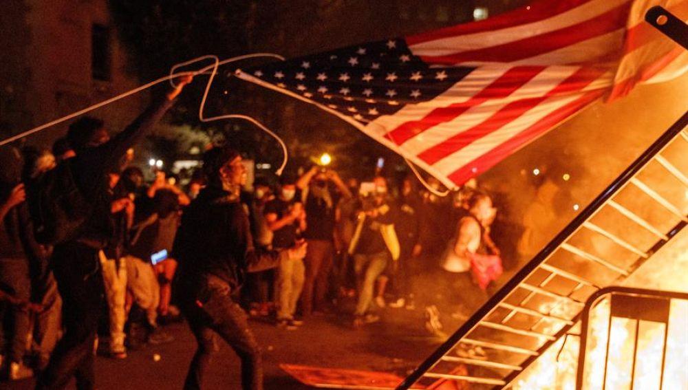 Arrojan una bandera de Estados Unidos al fuego durante una manifestación