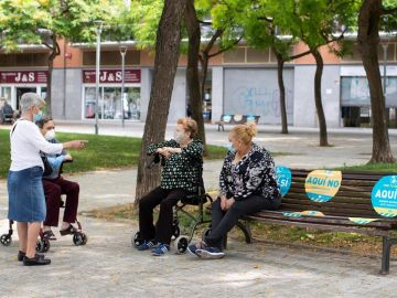 Varias mujeres mantienen la distancia social mientras hablan en una calle de Barcelona.