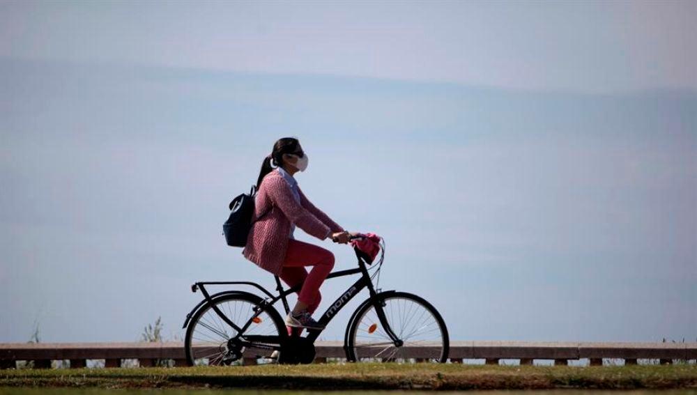 Una mujer con mascarilla pasea en bicicleta durante la desescalada