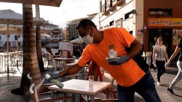 Un camarero desinfecta unas sillas de una terraza de un bar.