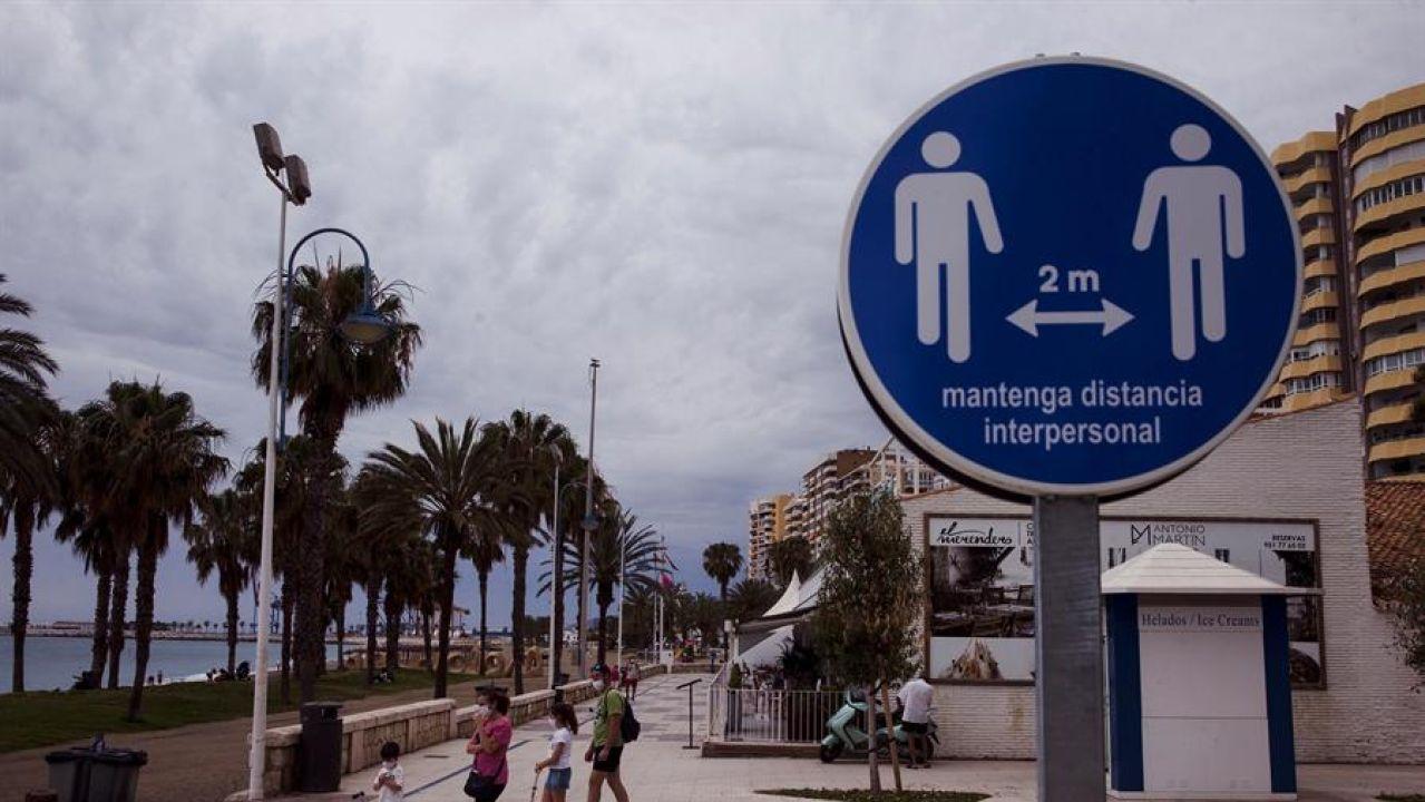 Una familia en el paseo marítimo de la Malagueta ante un disco que recuerda mantener la distancia de 2 metros entre personas