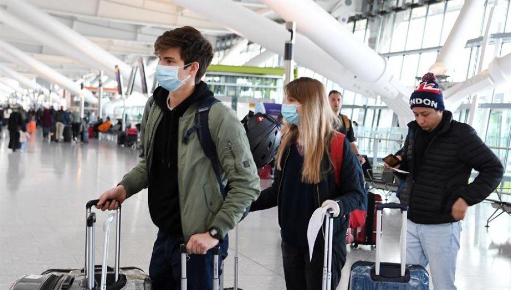 Pasajeros con mascarilla en un aeropuerto