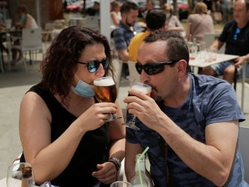 Una pareja disfruta de una cerveza en una terraza de Madrid