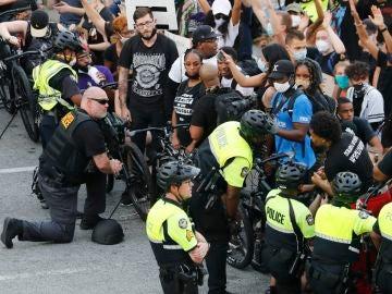 Policías se arrodillan frente a manifestantes que protestan contra la violencia racial