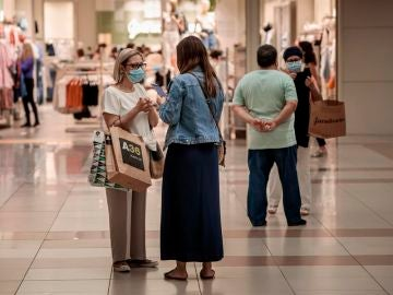 Personas con mascarilla compran en un centro comercial