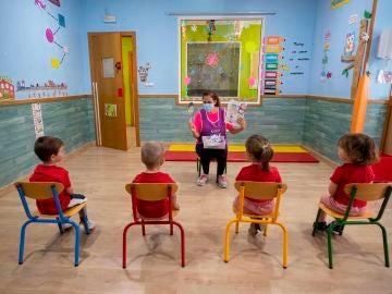 Una educadora de un centro de educación infantil les cuenta un cuento a varios niños y niñas en Murcia