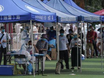 Residentes o gente que visitó el mercado de Xinfadi hacen cola para hacerse el test de coronavirus en el pabellón deportivo de Guang'an en Pekín.