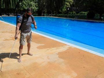Un operario desinfecta el perímetro de una piscina.