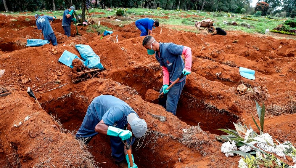 Sepultureros del cementerio de Vila Formosa, el más grande de América Latina, abren nuevas fosas este lunes para realizar más entierros dada la pandemia COVID-19, en Sao Paulo (Brasil)