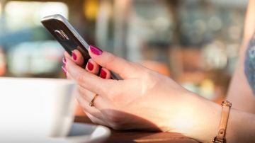Imagen de una mujer usando un teléfono móvil en un bar