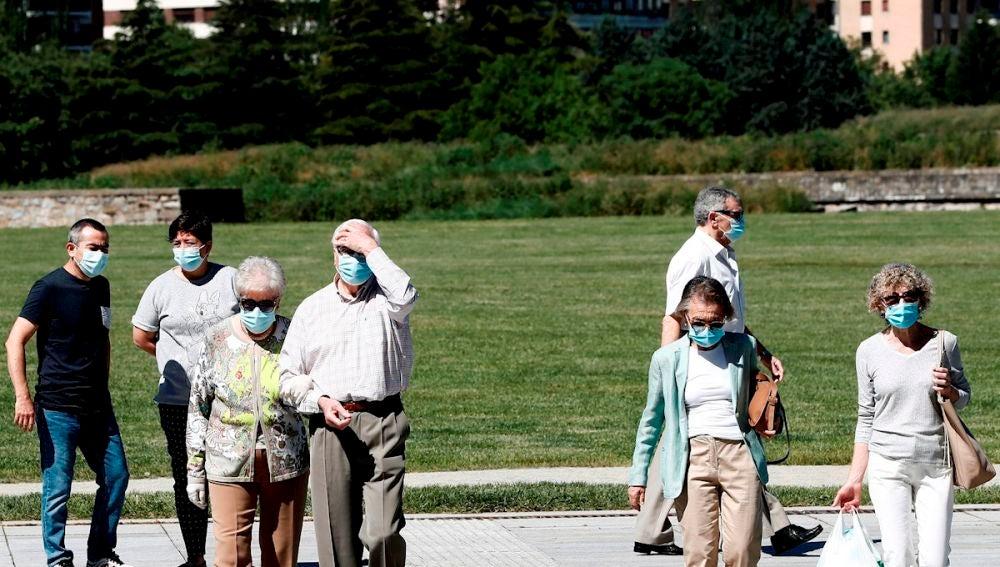 Un grupo de personas con mascarilla pasean por un parque