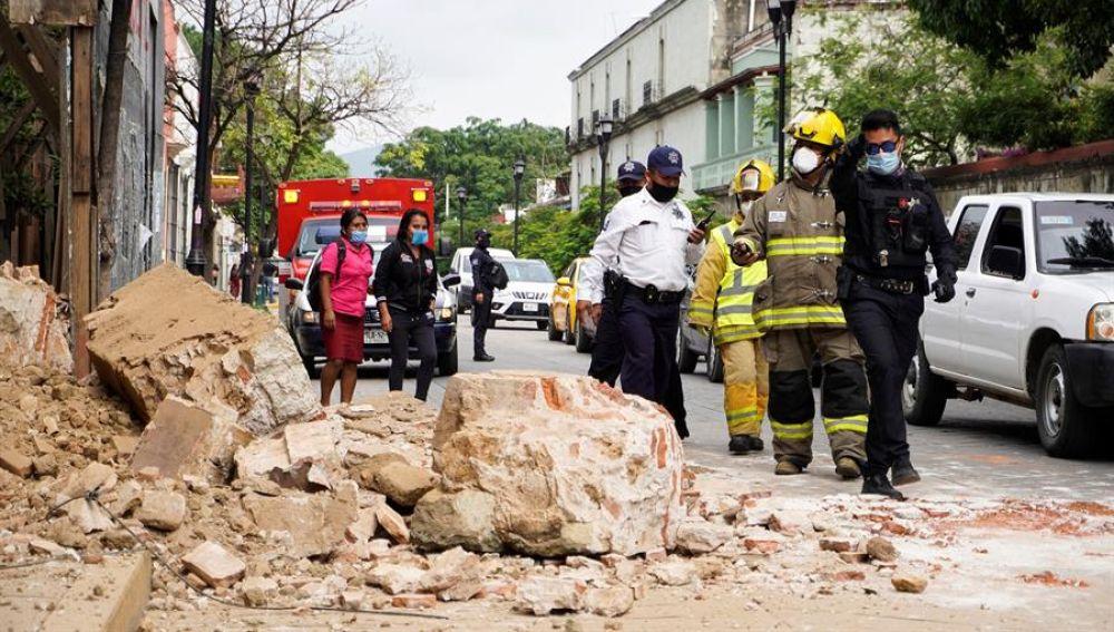 Miembros de la policía y de los bomberos observan los daños causados en un derrumbe en la ciudad de Oaxaca (México).