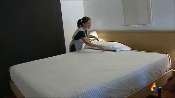 Una camarera de piso limpiando una habitación de hotel