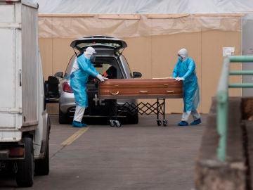 Trabajadores de una funeraria cargan un ataúd en el Hospital San José en Santiago (Chile)