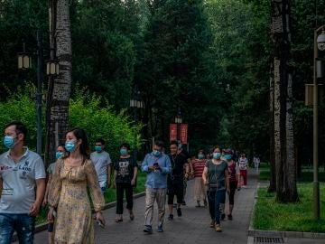 Un grupo de personas con mascarilla pasea por Pekín