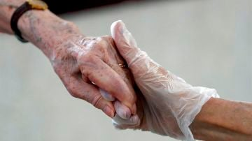 Una sanitaria da la mano a una anciana en una residencia