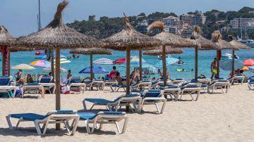 Imagen de unas sombrillas y hamacas vacías en la arena en una playa