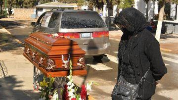 Una mujer espera junto a un féretro afuera de un cementerio