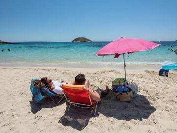 Una pareja toma el sol en la Playa de Magaluf, en Mallorca.