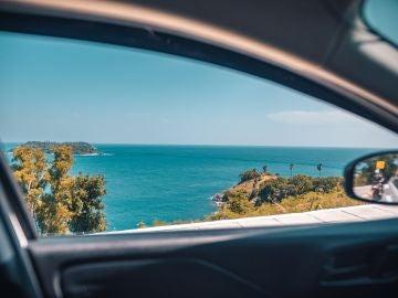 Vistas del mar desde la ventanilla lateral de un coche