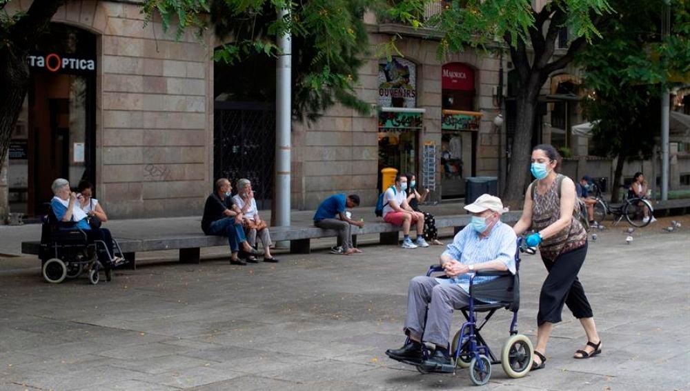 Una mujer empuja la silla de un señor mayor en el centro de Barcelona.