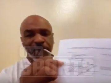 Mike Tyson muestra el contrato de su vuelta al ring mientras se fuma un porro