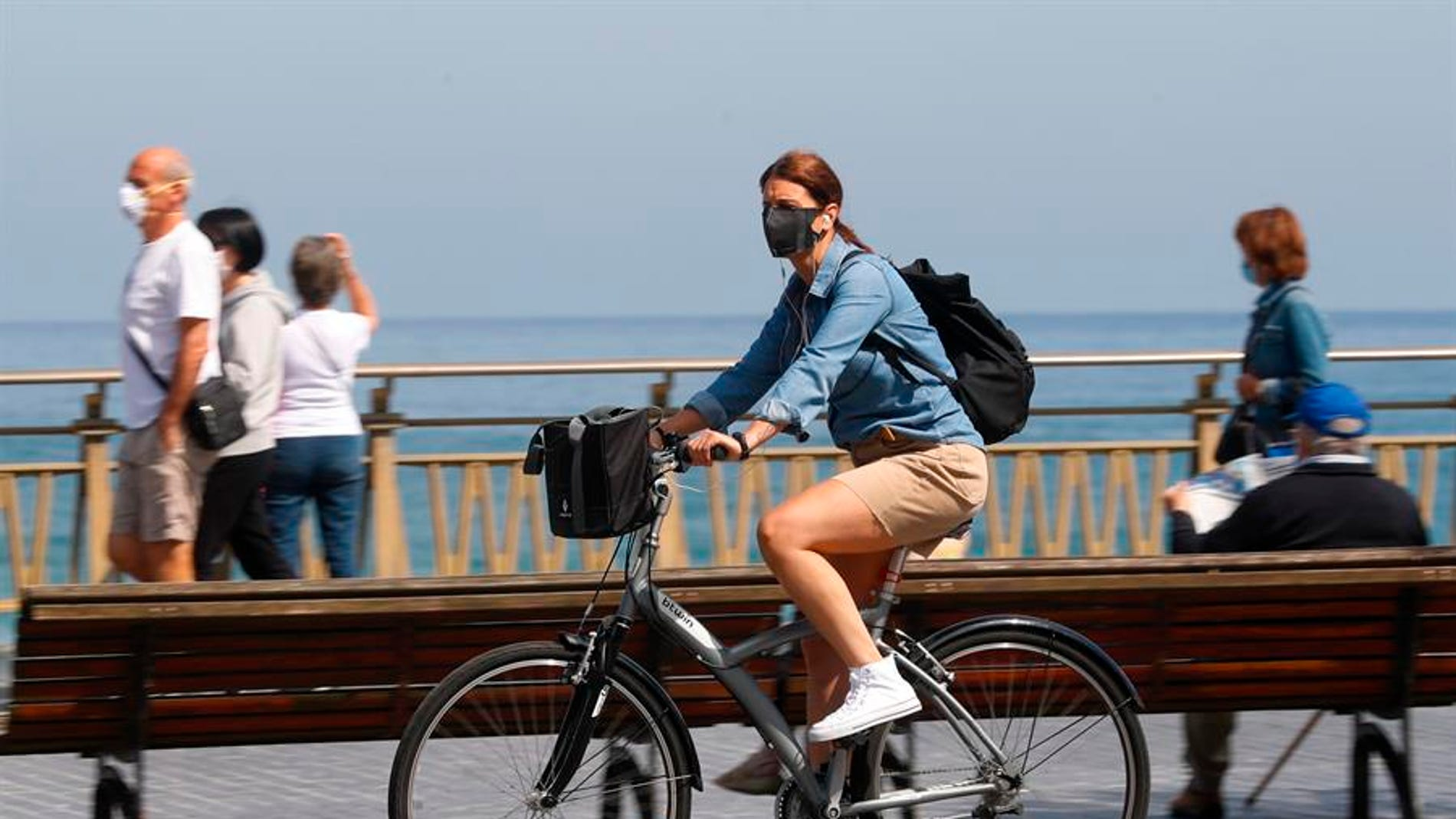 Una mujer pasea en bicicleta protegida con una mascarilla por el paseo de la Zurriola de San Sebastián