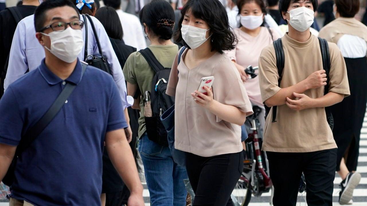 Peatones con mascarilla en una calle de Tokio