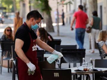 Un camarero desinfecta una mesa tras las marcha de los clientes la terraza de un bar del centro de Madrid
