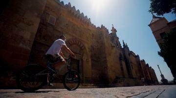 Un hombre hace turismo en bicicleta pasa junto la Mezquita-Catedral en Córdoba