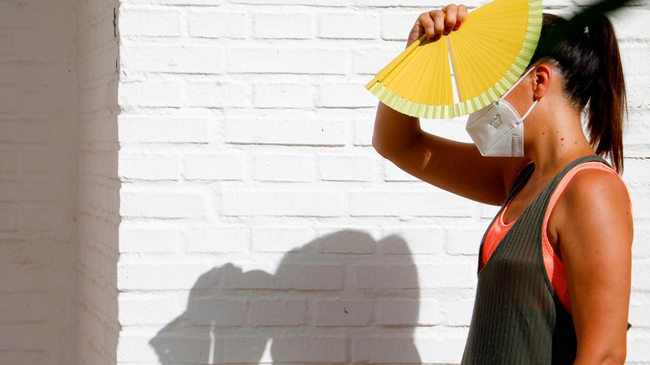 Una mujer se protege del sol con un abanico