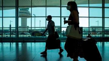Viajeros con máscaras caminan por la Terminal 1 del aeropuerto Josep Tarradelles - El Prat