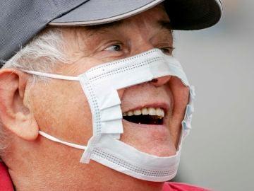 Un manifestante luce una mascarilla recortada como protesta contra las medidas y restricciones impuestas por el coronavirus durante una manifestación en los campos de Malieveld en La Haya