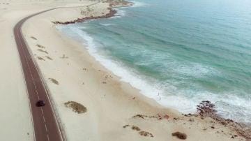 Un coche recorre una carretera a pie de playa en Fuerteventura