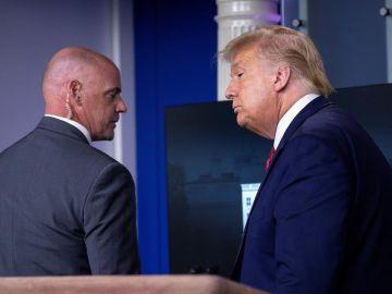 El presidente de Estados Unidos, Donald Trump, escoltado fuera de una rueda de prensa.