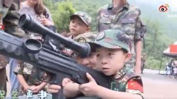 Un niño chino sostiene un arma durante una visita a un centro de entrenamiento militar