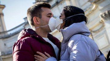 Dos jóvenes besándose con mascarilla