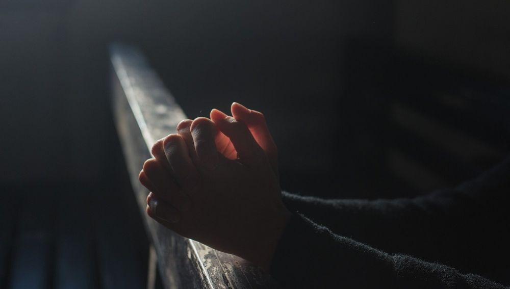 Imagen de archivo de una persona rezando en la iglesia