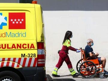 Una sanitaria lleva a un paciente en silla de ruedas